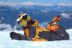 Ragazzo con i vestiti del pattino in alpi Immagine Stock