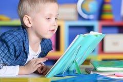 Ragazzo con i vetri ed i libri che fanno le lezioni Immagini Stock