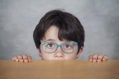 Ragazzo con i vetri su una tavola di legno Immagine Stock