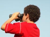 Ragazzo con il binocolo fotografia stock
