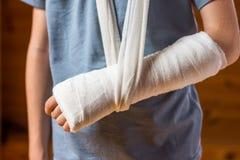 Ragazzo con il braccio in gesso nei precedenti marroni Immagine Stock Libera da Diritti