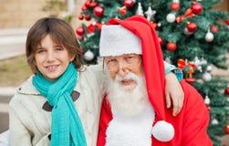 Ragazzo con il braccio intorno a Santa Claus Outdoors Fotografia Stock