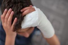 Ragazzo con il braccio rotto che tocca testa immagini stock libere da diritti