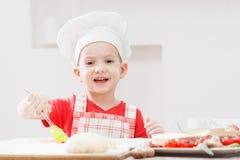 Ragazzo con il cappello del cuoco unico che prepara la pasta della pizza Fotografie Stock