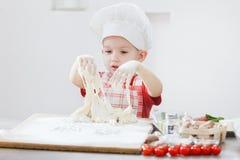 Ragazzo con il cappello del cuoco unico che prepara la pasta della pizza Fotografie Stock Libere da Diritti