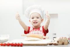 Ragazzo con il cappello del cuoco unico che prepara la pasta della pizza Immagine Stock