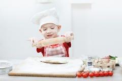 Ragazzo con il cappello del cuoco unico che prepara la pasta della pizza Immagini Stock Libere da Diritti