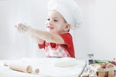 Ragazzo con il cappello del cuoco unico che prepara la pasta della pizza La farina è versata sulla tavola Fotografia Stock Libera da Diritti