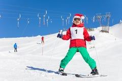 Ragazzo con il cappello del ` s di Santa che impara sciare nell'orario invernale Fotografie Stock Libere da Diritti