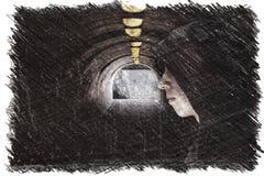 Ragazzo con il cappuccio che sta in un passaggio sotterraneo scuro con le lampadine della luce gialla al tetto ed alla luce all'e fotografie stock