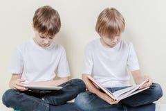 Ragazzo con il computer ed il bambino della compressa che leggono un libro Scherza il concetto di svago di istruzione Immagine Stock