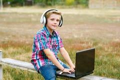 Ragazzo con il computer portatile e le cuffie da fare all'aperto Immagini Stock