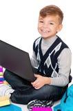 Ragazzo con il computer portatile ed i libri Immagine Stock