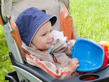 Ragazzo con il giocattolo nel passeggiatore all'esterno Fotografie Stock
