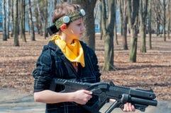 Ragazzo con il legame giallo che tiene pistola di plastica nera e che gioca il gioco del rimorchiatore del laser nella foresta di Fotografia Stock