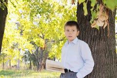 Ragazzo con il libro che osserva obliquamente fotografie stock