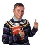 Ragazzo con il libro rosso che mostra i pollici in su Fotografia Stock Libera da Diritti