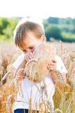 Ragazzo con il pane sopra la vostra testa nel grano maturo con la s Immagine Stock