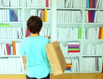 Ragazzo con il sacco di carta nel negozio del deposito di libro Immagini Stock