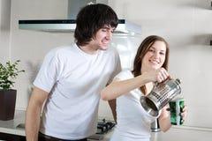 Ragazzo con il sorriso e la ragazza con la tazza e con la teiera Fotografie Stock