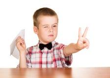 Ragazzo con l'aereo di carta che si siede ad una tavola isolata sul bianco Immagine Stock