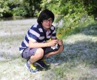 Ragazzo con l'allergia del polline con il fazzoletto bianco a disposizione Fotografia Stock