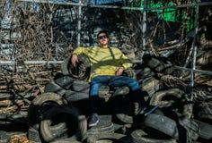Ragazzo con l'attrezzatura urbana che si siede su una montagna di vecchie gomme immagini stock