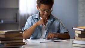 Ragazzo con l'inabilità per imparare le abilità di scrittura e della lettura che provano a concentrarsi fotografie stock
