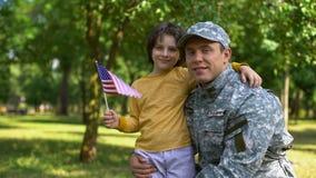 Ragazzo con la bandiera americana che abbraccia l'uniforme militare del padre, festa dell'indipendenza, onore archivi video