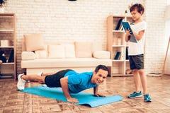 Ragazzo con la compressa ed il padre Doing Push Ups sul pavimento immagini stock libere da diritti