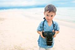 Ragazzo con la macchina fotografica della foto sulla priorità bassa della spiaggia immagine stock