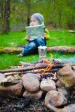 Ragazzo con la mappa che si siede vicino ad un fuoco di accampamento Immagini Stock Libere da Diritti
