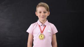 Ragazzo con la medaglia, risultato prominente nell'istruzione, competizione sportiva di conquista video d archivio