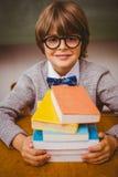 Ragazzo con la pila di libri in aula Fotografia Stock