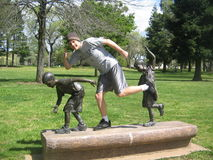 Ragazzo con le statue dei ragazzi in Redding, parco di California immagini stock libere da diritti
