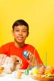Ragazzo con le uova di Pasqua ed il coniglio sveglio sulla tavola Immagine Stock