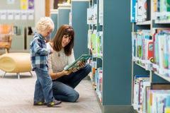 Ragazzo con lo scaffale per libri di Selecting Book From dell'insegnante Fotografie Stock Libere da Diritti