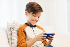 Ragazzo con lo smartphone che manda un sms o che gioca a casa Fotografia Stock