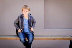 Ragazzo con lo zaino che si siede sul banco vicino alla scuola fotografia stock libera da diritti
