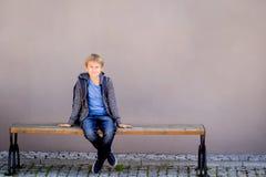 Ragazzo con lo zaino che si siede sul banco vicino alla scuola fotografia stock