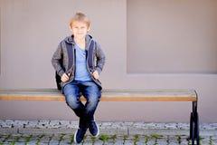 Ragazzo con lo zaino che si siede sul banco vicino alla scuola Fotografie Stock Libere da Diritti