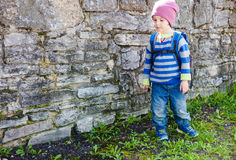 Ragazzo con lo zaino che sta vicino ad una parete di pietra Fotografie Stock Libere da Diritti