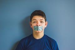 Ragazzo con nastro adesivo di condotta sopra la sua bocca Immagine Stock