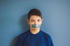 Ragazzo con nastro adesivo di condotta sopra la sua bocca Fotografie Stock Libere da Diritti