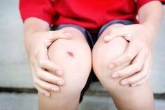Ragazzo con un ginocchio raschiato immagini stock