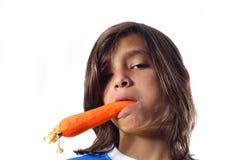 Ragazzo con una carota nella sua bocca fotografia stock libera da diritti