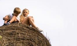 Ragazzo con una ragazza che si siede sul mucchio di fieno i precedenti del cielo Fotografie Stock