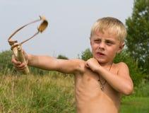 Ragazzo con uno slingshot. Immagini Stock