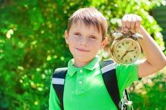 Ragazzo con uno zaino e un orologio in mani Immagini Stock