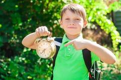 Ragazzo con uno zaino e un orologio in mani Fotografie Stock Libere da Diritti